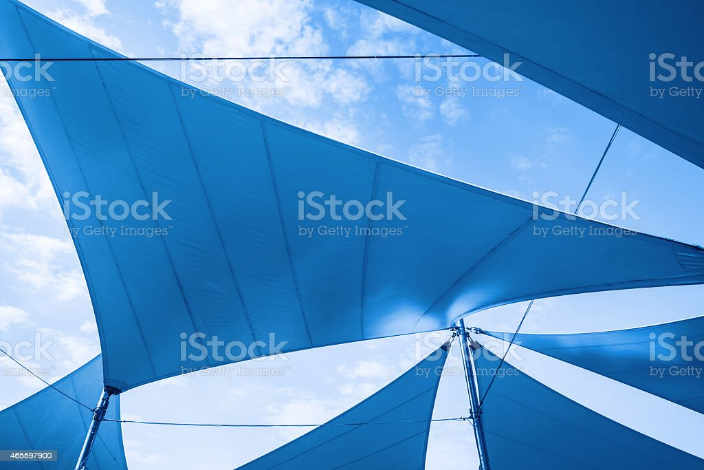 Awnings in sails shape over cloudy sky stock photo