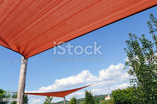 stretched rust coloured awnings before blue sky