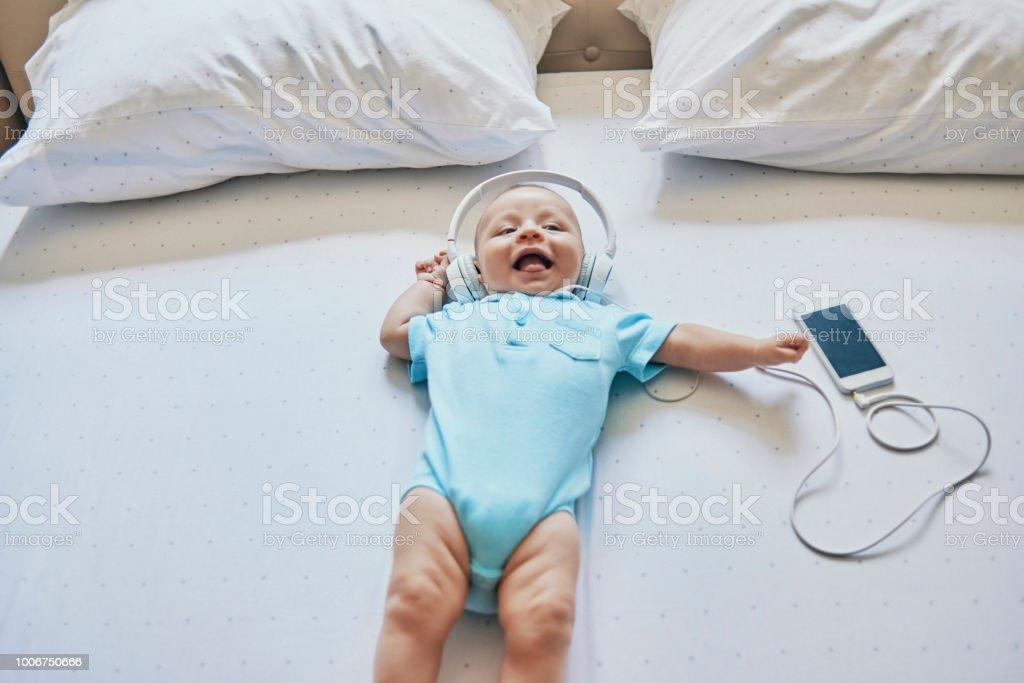 awsome baby enjoying listening to music stock photo