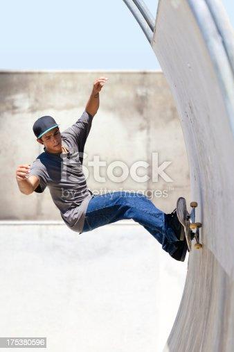 XXXL.  Young man doing a skateboard trick at a skateboard park.