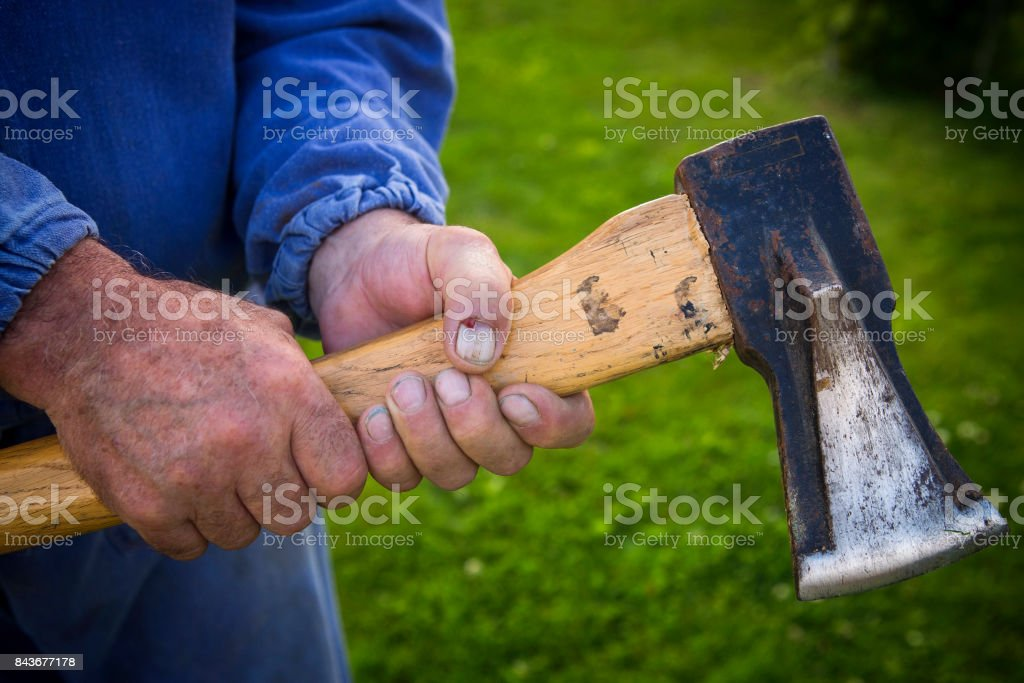 Ax in the hands of rough labor stock photo