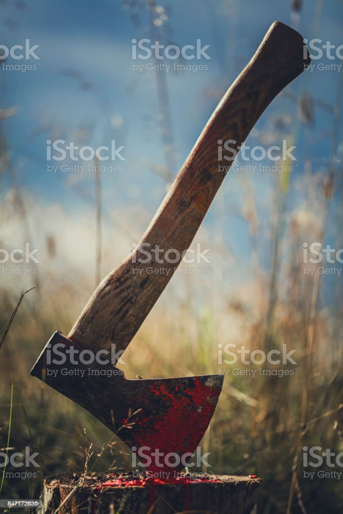 Axe in stump - blood traces stock photo