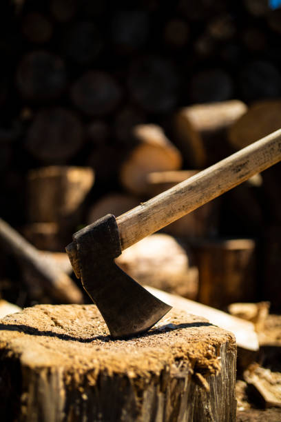 A axe stuck in a piece of wood stock photo