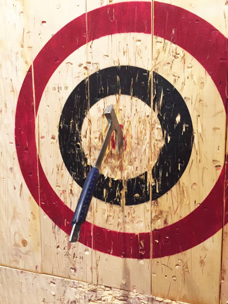 Axe Throwing at Targets A large metal ax is embedded into a wooden target while playing the game of axe throwing. throwing stock pictures, royalty-free photos & images