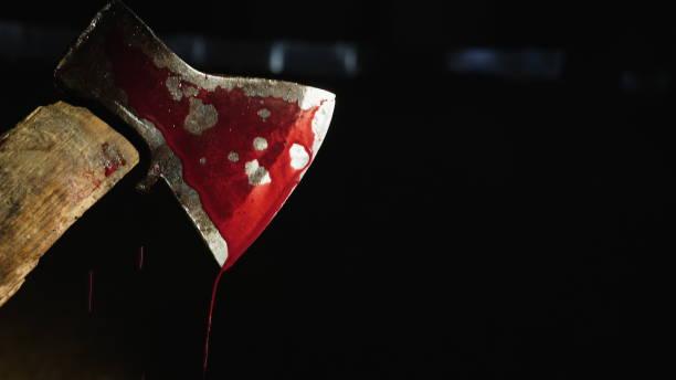 bijl met bloed in de hand op de donkere achtergrond - moordenaar stockfoto's en -beelden
