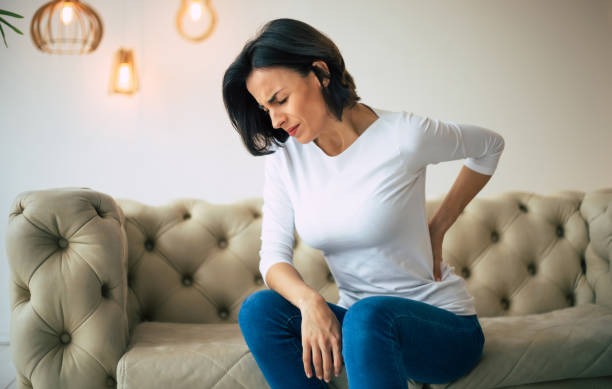 Axial pain. Close-up photo of a hurting woman, who is sitting on a couch and holding her lower back with her left hand. A hurting woman, who is sitting on a couch and holding her lower back with her left hand. back pain stock pictures, royalty-free photos & images
