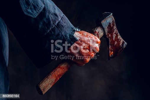 Male hand holding bloody axe. Halloween theme.