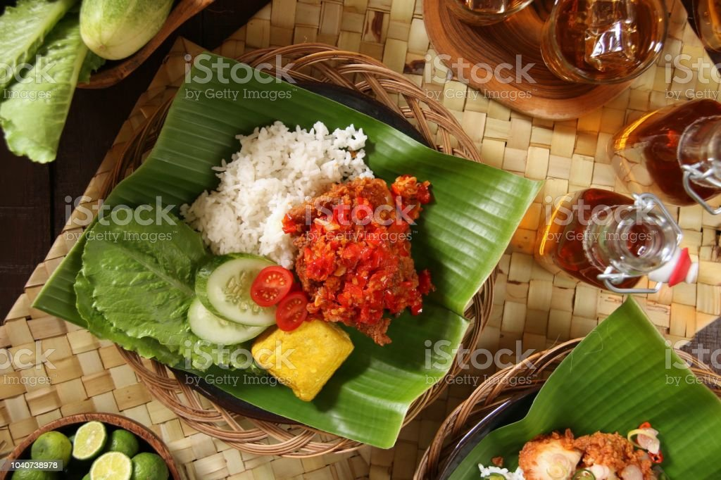 Ayam Geprek Balado, Fusion Street Food of Southern Fried Chicken with Crushed Red Chili Paste from West Sumatra stock photo