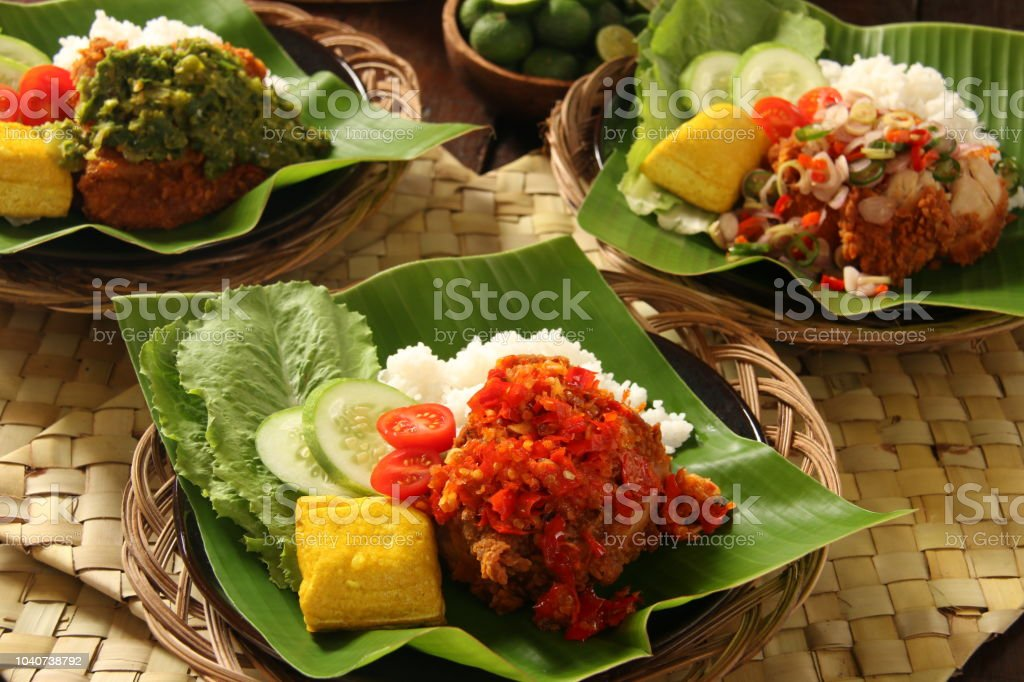 Ayam Geprek, Fusion Street Food of Southern Fried Chicken with Traditional Indonesian Spicy Condiments stock photo