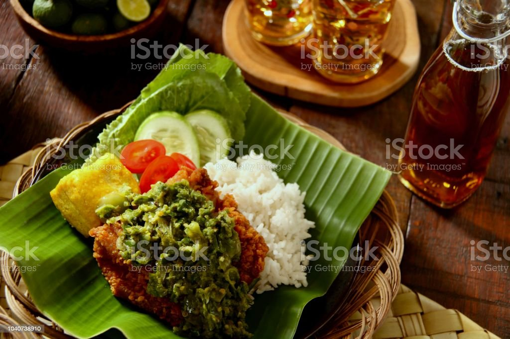 Ayam Geprek Lado Mudo, Fusion Street Food of Southern Fried Chicken with Crushed Green Chili Paste from West Sumatra stock photo