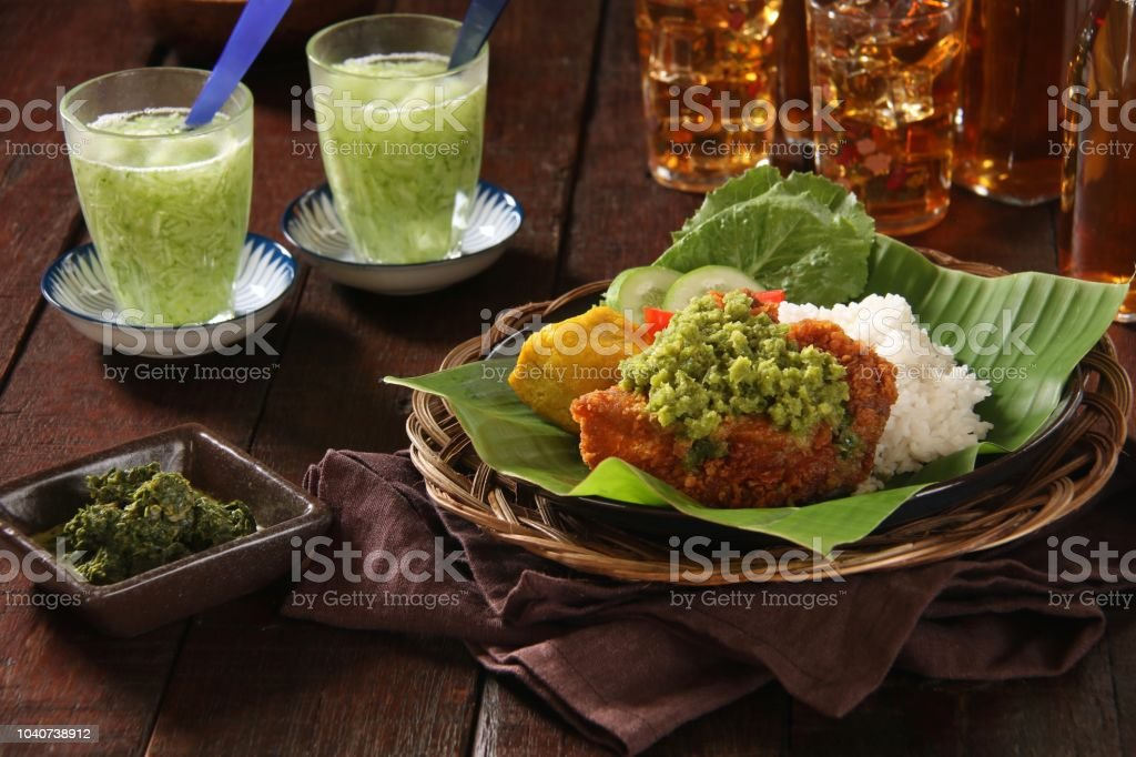 Ayam Geprek Sambal Andaliman, Fusion Street Food of Southern Fried Chicken with Green Chili and Andaliman Peppercorn Paste from North Sumatra stock photo
