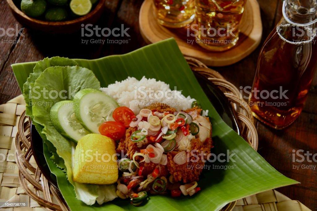 Ayam Geprek Sambal Matah, Fusion Street Food of Southern Fried Chicken with Balinese Salsa of Chili Peppers, Lemon Grass and Shallots stock photo