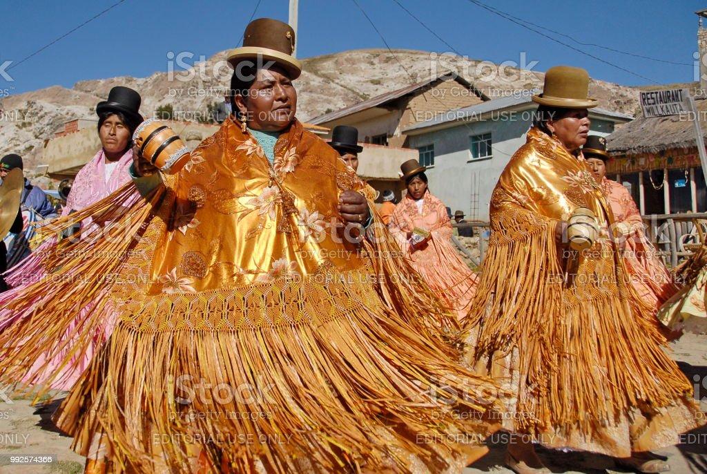 Aymara women dance traditional dance at festival Morenada, Isla del Sol, Lake Titicaca, Bolivia. stock photo