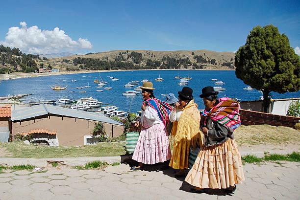 Aymara women pass by public pier in Copacabana, Bolivia. stock photo