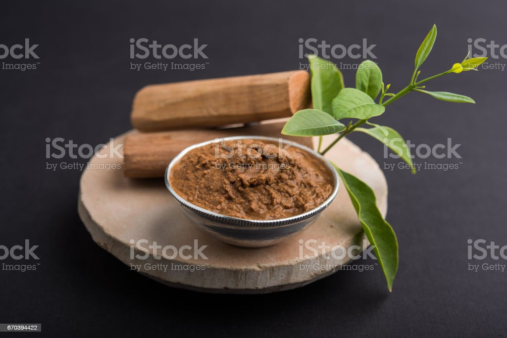 Ayurvedic Chandan powder or sandalwood paste in silver bowl with sticks and leaves placed over sahan or sahana or circular stone base for creating paste stock photo