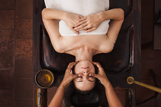 Ayurvedic face massage with oil on the wooden table​​​ foto