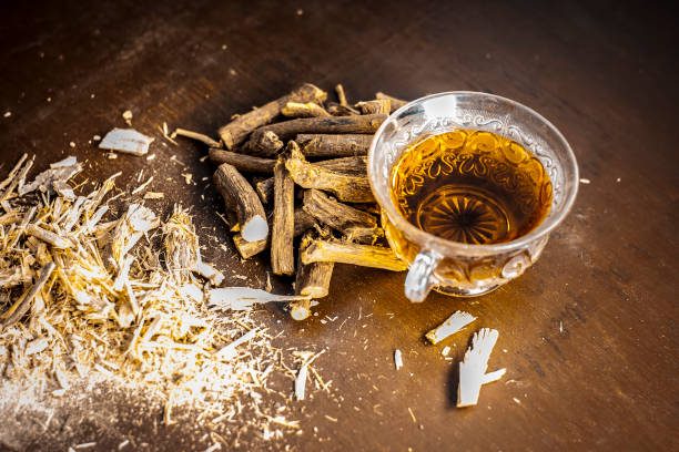 ayurvedic herb liquorice root,licorice root, mulethi or glycyrrhiza glabra root and its powder with its tea for detoxifying the body, soothing spasms, easing menstrual cramps, raising blood pressure. - liquirizia foto e immagini stock