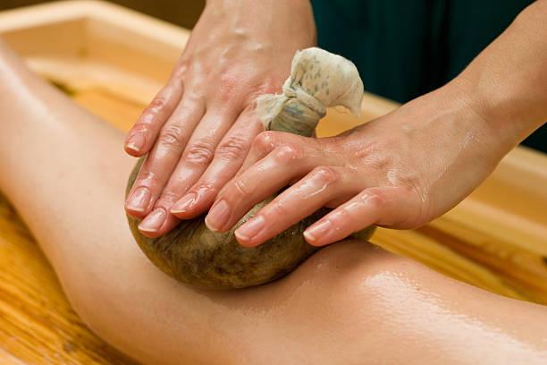 Ayurvedic oil massage on a wooden table stock photo