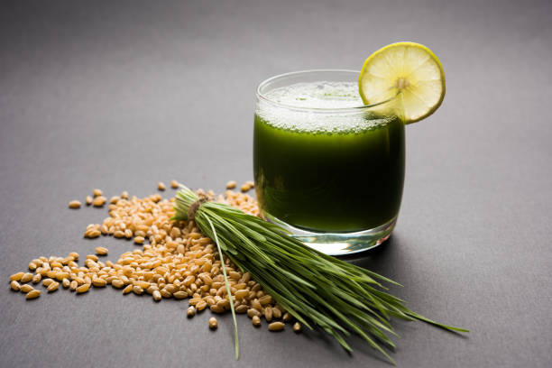 Ayurvedic or medicinal Wheat grass juice with lemon slice in glass, selective focus Ayurvedic or medicinal Wheat grass juice with lemon slice in glass, selective focus chlorophyll stock pictures, royalty-free photos & images