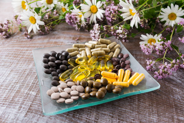 Ayurvedic pills with chamomile and tansy flowers stock photo