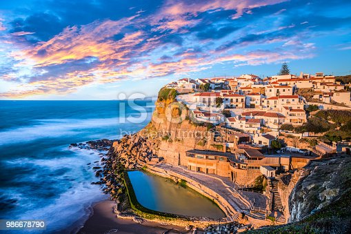 The image shows a beautiful place in Azenhas do mar, in Sintra, near Lisbon on a great sunset with a natural pool.