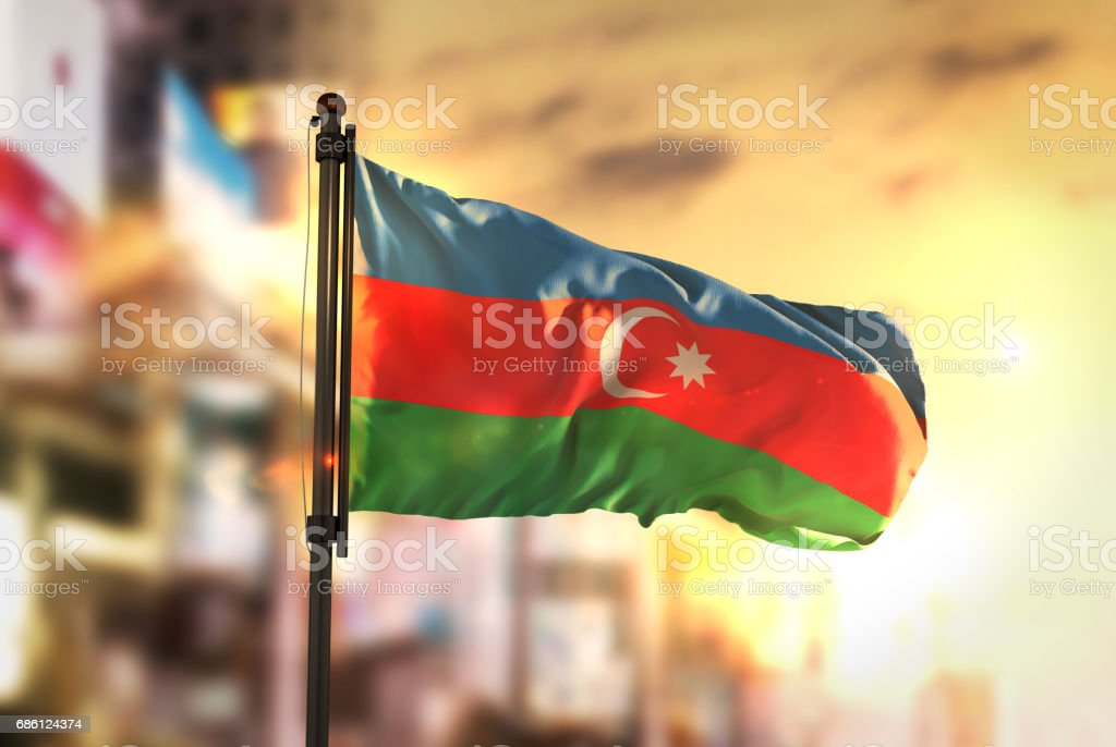Azerbaijan Flag Against City Blurred Background At Sunrise Backlight stock photo