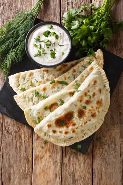 Azerbaijani food: flatbread qutab with greens and yogurt close-up. Vertical top view stock photo