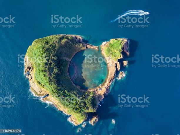 Photo of Azores aerial panoramic view. Top view of Islet of Vila Franca do Campo. Crater of an old underwater volcano. San Miguel island, Azores, Portugal. Heart carved by nature. Bird eye view.