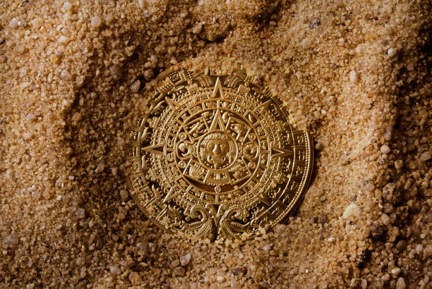 Aztec coin. Aztec coin laying in sand upper view. antiquities stock pictures, royalty-free photos & images