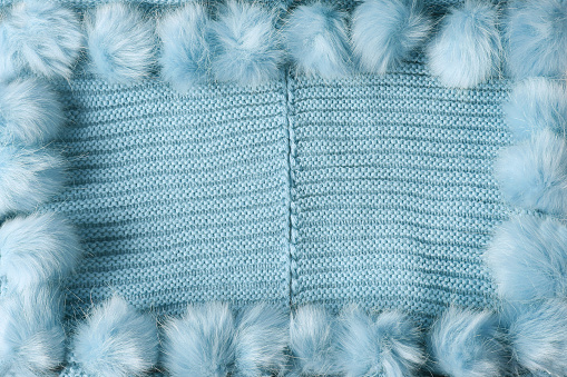 Azure light blue winter textile background with copy space and a frame with fluffy tassels