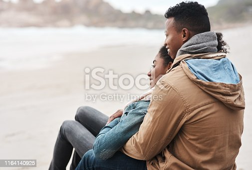 Shot of a young couple sitting on the beach on a cloudy day