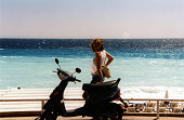 A beach babe leaning on a moto