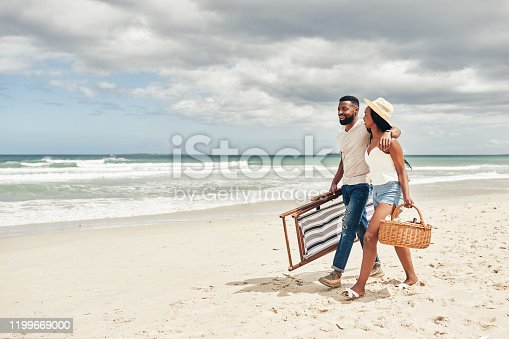 Shot of an affectionate young couple walking on the beach
