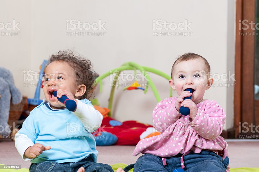 Babies Enjoying Playtime Chewing on their Rattles stock photo