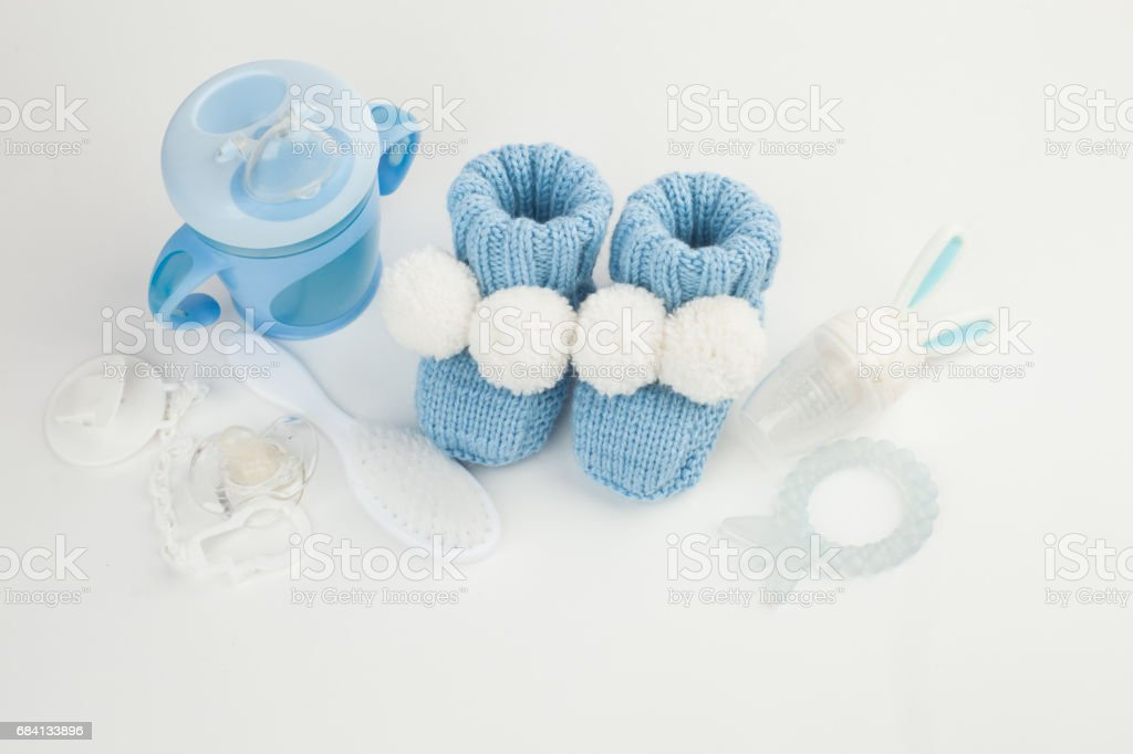 Babies goods: booties, nibbler, cream, soother, drinker and toy on white background, front view foto stock royalty-free
