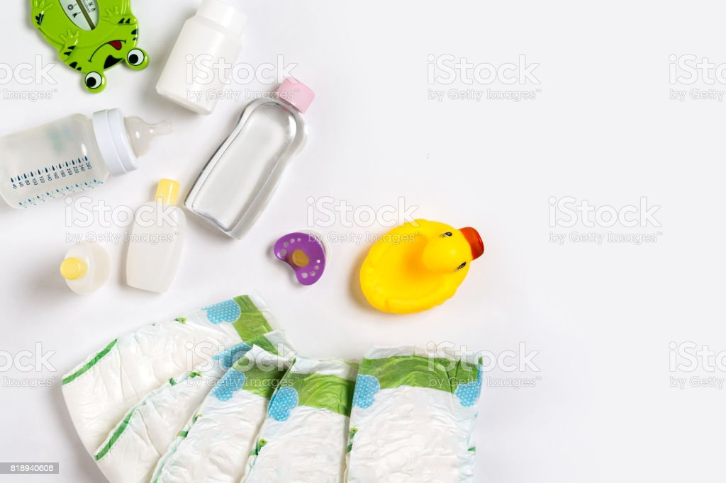 Babies goods diaper, baby powder, cream, shampoo, oil on white background with copy space. Top view or flat lay stock photo