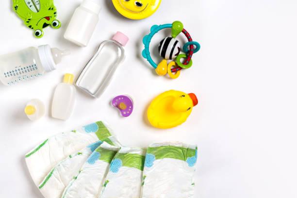 赤ちゃん用品おむつ、ベビー パウダー、クリーム、シャンプー、コピー領域の白い背景の上の油。トップ ビューまたはフラット レイアウト ストックフォト