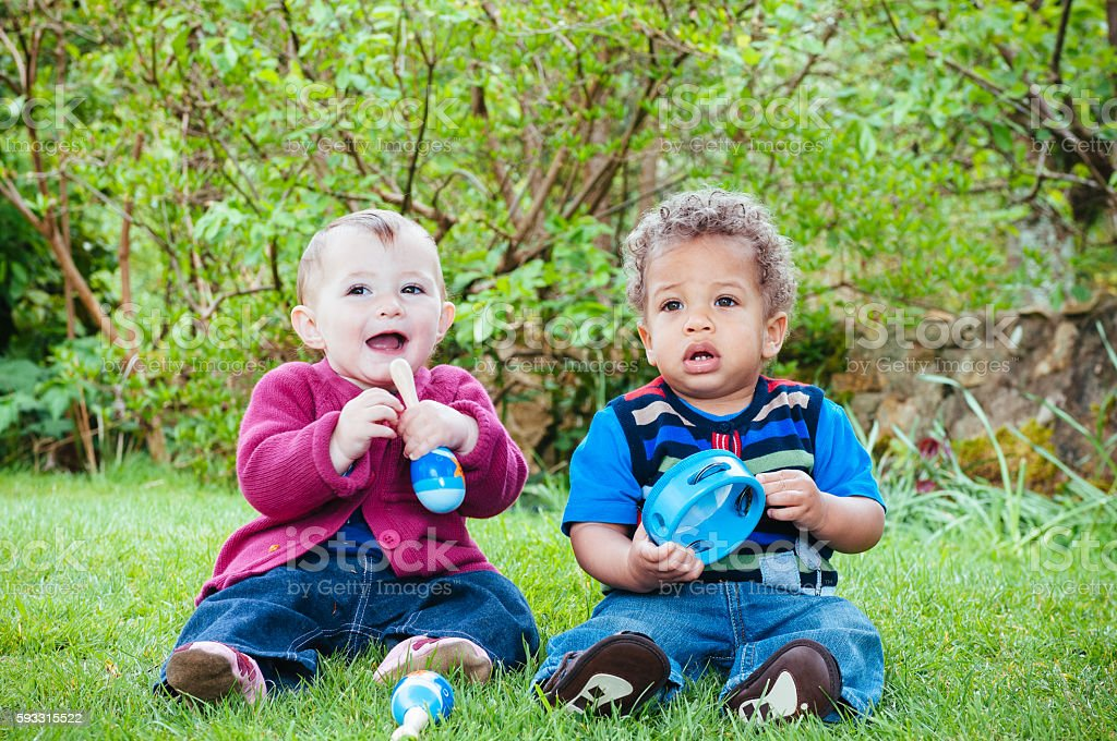 Babies looking at the camera and smiling while playing maracas stock photo