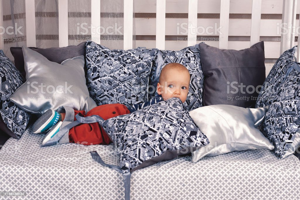 A boy up to a year are sitting on a bed with pillows.
