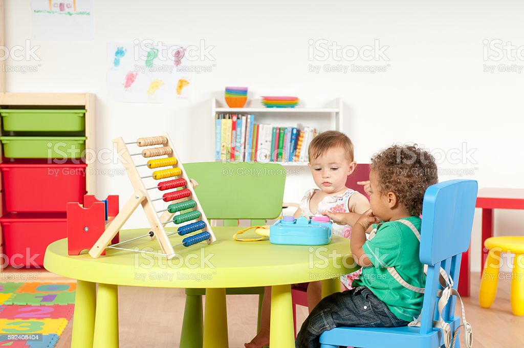 Babies Playing in a Nursery Together stock photo