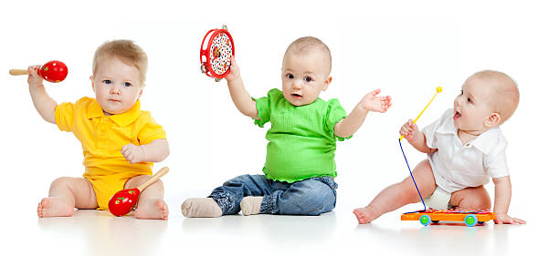 Babies playing with musical toys stock photo