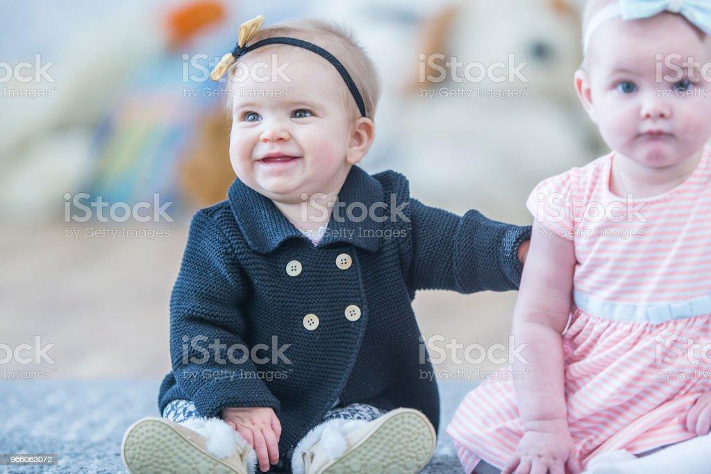 Spädbarn som sitter tillsammans - Royaltyfri 12-23 månader Bildbanksbilder