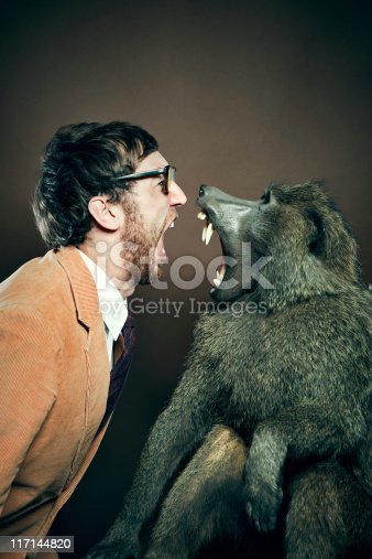 A man and ape scream at each other, face to face, nose to nose.  Vertical with copy space.  Man is wearing a corduroy blazer, tie, and thick glasses.  Vertical with copy space.