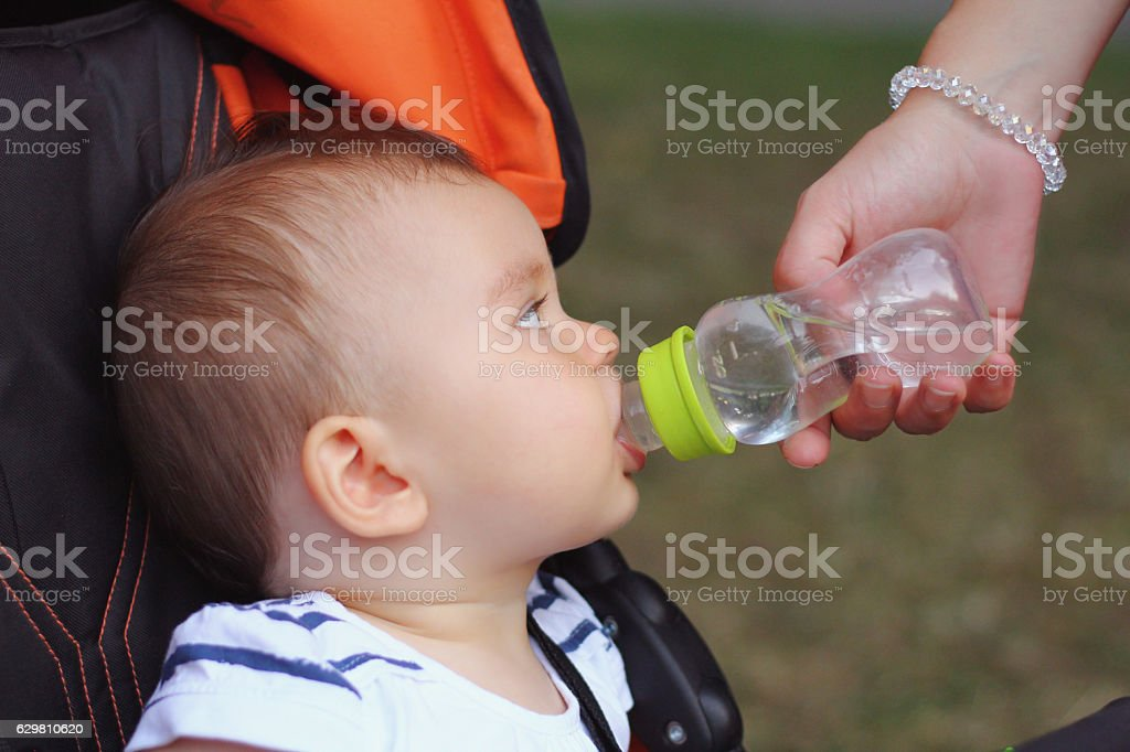 Babv sitting in a strolle feeding with a water bottle. stock photo