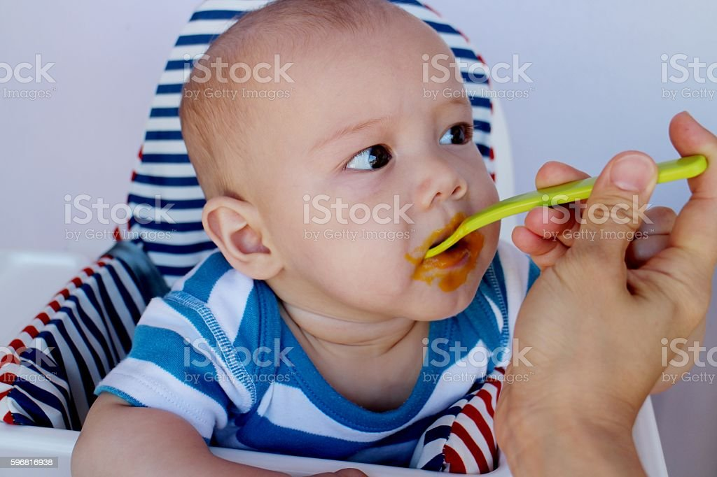 Baby 6 months old eat first food puree stock photo