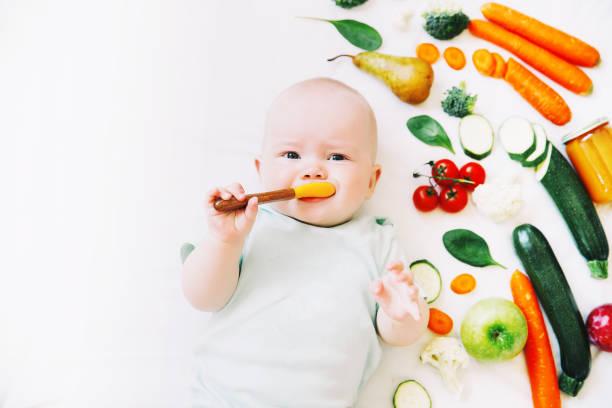 Bebé 8 meses rodeado de diferentes frutas y verduras frescas sobre fondo blanco. - foto de stock