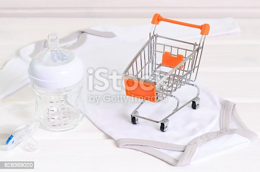 istock baby accessories  and shopping basket on white wooden background 628369020