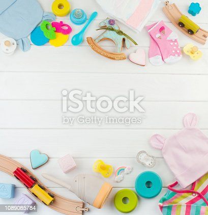 Baby accessories and toys on white wooden background with blank space for text; top view, flat lay