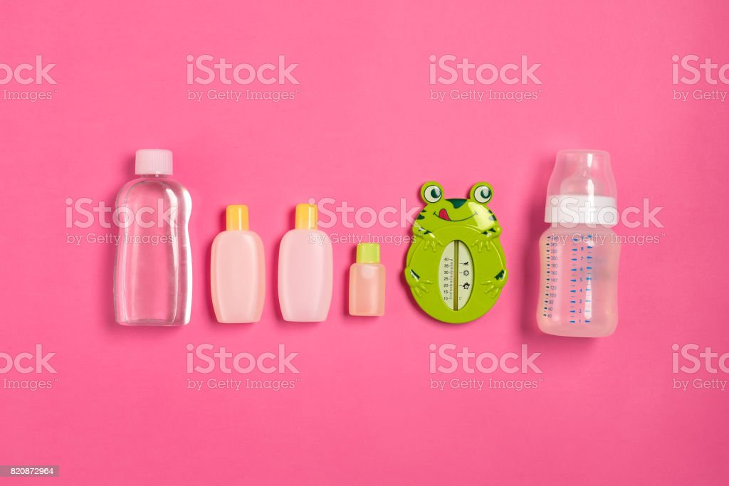 Baby accessories for bath with frog on pink background. Top view stock photo