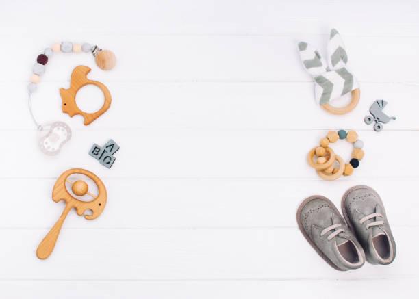 baby-accessoires auf weißem holz hintergrund - babyschuh stock-fotos und bilder